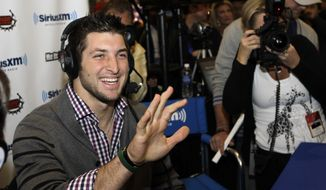**FILE** Denver Broncos quarterback Tim Tebow waves to actress Jenny McCarthy during an interview with Sirius XM radio on radio row at the Super Bowl XLVI media center Friday, Feb. 3, 2012, in Indianapolis. The New England Patriots will face the New York Giants in Super Bowl XLVI on Feb. 5. (AP Photo/David J. Phillip)