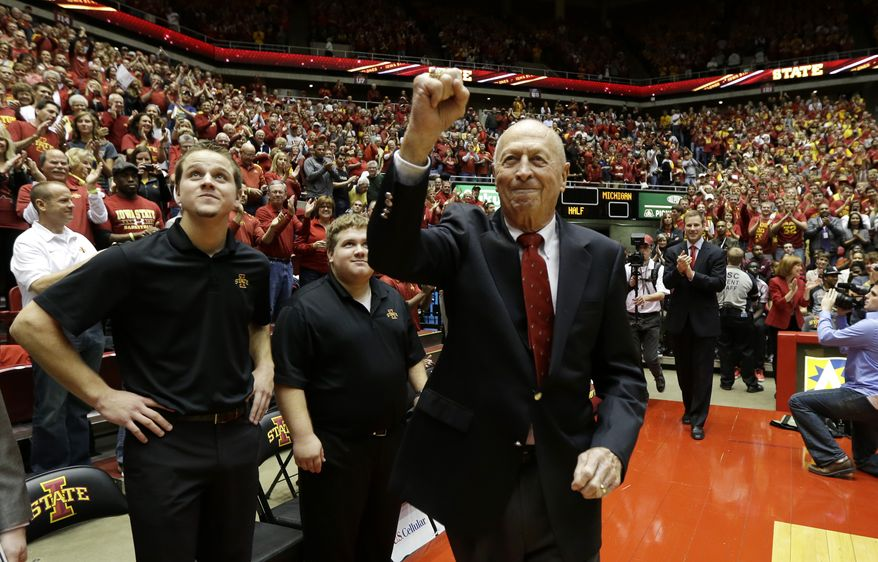 Former Iowa State basketball coach Johnny Orr pumps his fist as we walks onto the court before an NCAA college basketball game between Iowa State and Michigan, Sunday, Nov. 17, 2013, in Ames, Iowa. Iowa State won 77-70. (AP Photo/Charlie Neibergall)
