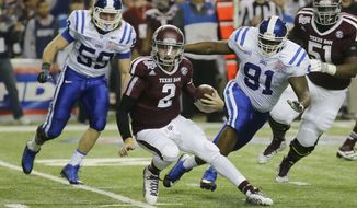 Texas A&M quarterback Johnny Manziel (2) is chased by Duke linebacker Kelby Brown (59) and nose tackle Jamal Bruce (91) in the first half of the Chick-fil-A Bowl NCAA college football game Tuesday, Dec. 31, 2013, in Atlanta. (AP Photo/Jamie Martin)