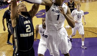 Kansas State's Shane Southwell (1) tries to block a shot by George Washington's Kevin Larsen during the first half of an NCAA college basketball game Tuesday, Dec. 31, 2013, in Manhattan, Kan. (AP Photo/Charlie Riedel)