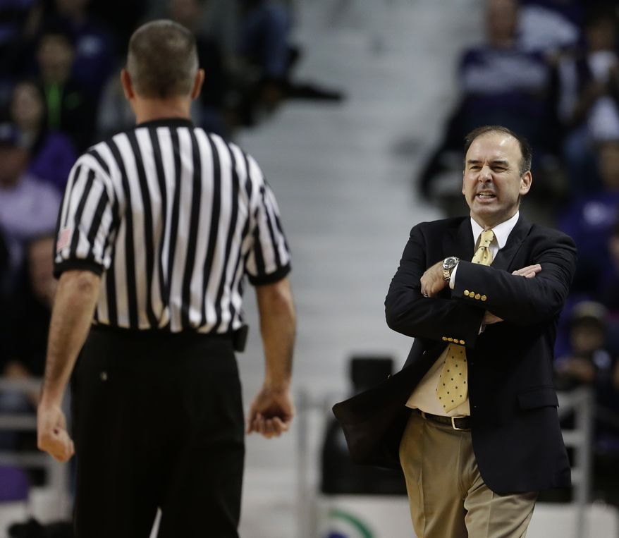 George Washington coach Mike Longeran talks to an official before being whistled for a technical foul during the second half of an NCAA college basketball game against Kansas State  on Tuesday, Dec. 31, 2013, in Manhattan, Kan. Kansas State won 72-55. (AP Photo/Charlie Riedel)
