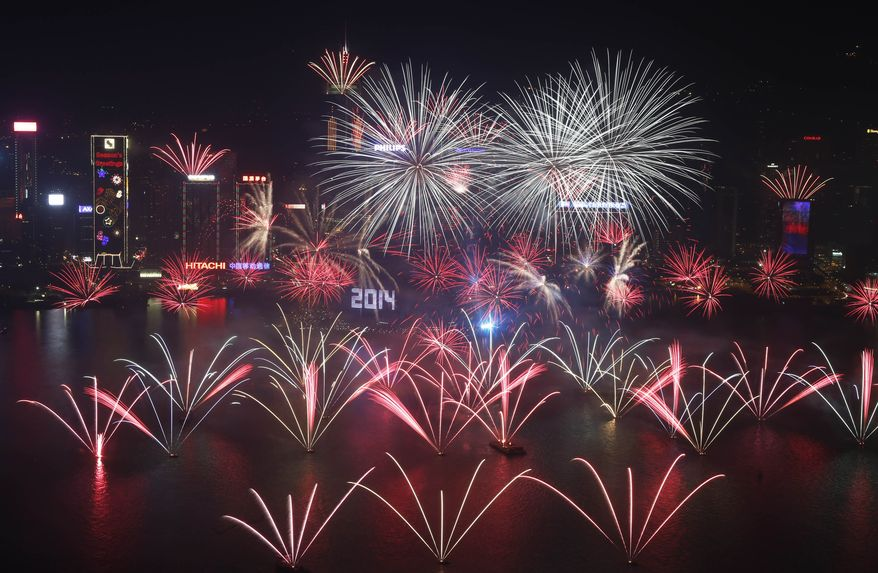 Fireworks explode at the Hong Kong Convention and Exhibition Centre over the Victoria Harbor during New Year's Eve to celebrate the start of 2014 in Hong Kong, Wednesday, Jan. 1, 2014 (AP Photo/Kin Cheung)