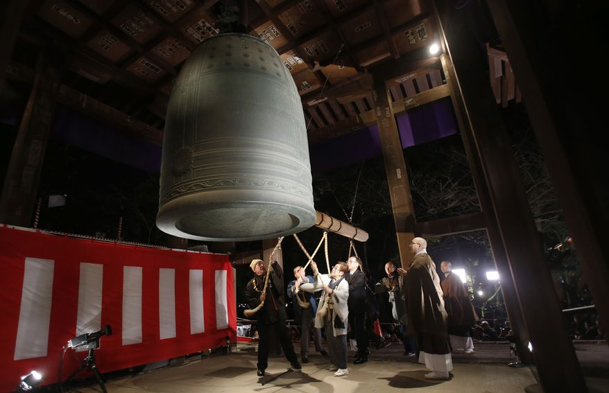 People strike a giant bell to celebrate the New Year at Zojoji Buddhist temple, in Tokyo, early Wednesday, Jan. 1, 2014. (AP Photo/Shizuo Kambayashi)