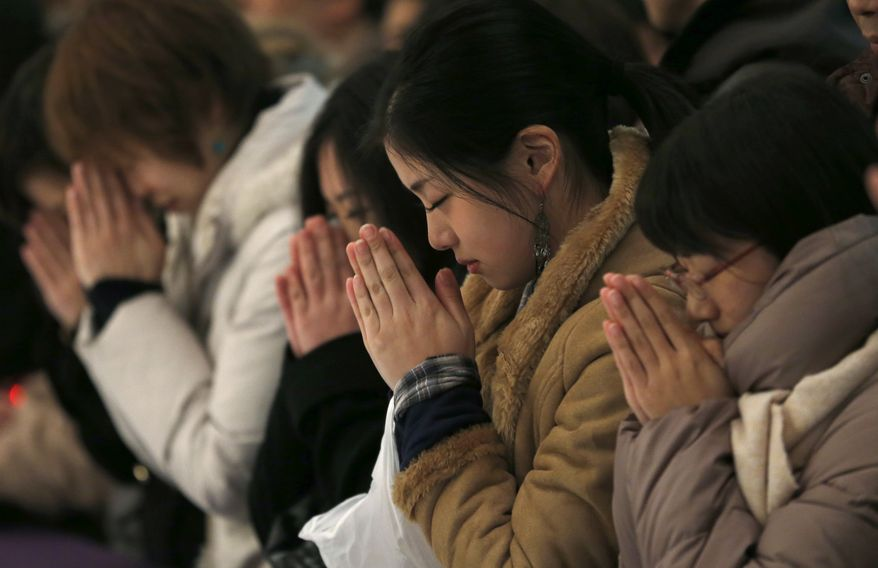 People pray at the start of the New Year at Zojoji Buddhist temple in Tokyo, early Wednesday, Jan. 1, 2014. (AP Photo/Shizuo Kambayashi)
