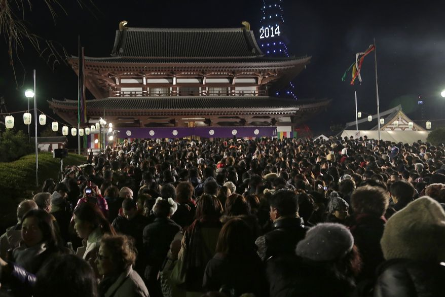 People gather at the Zojoji Buddhist temple in Tokyo to celebrate the New Year, early Wednesday, Jan. 1, 2014. (AP Photo/Shizuo Kambayashi)