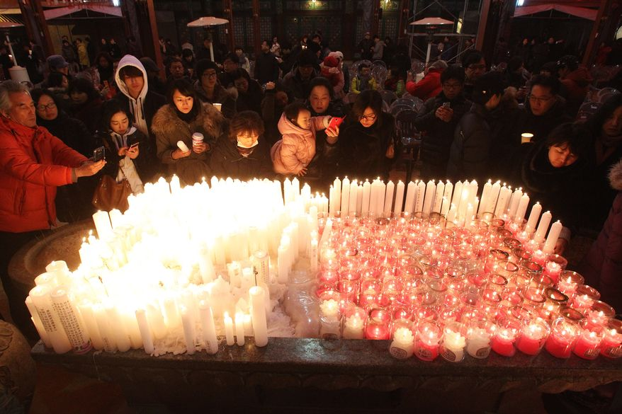 Buddhists light candles during New Year's Eve celebrations at Bongeun Buddhist temple in Seoul, South Korea, Wednesday, Jan. 1, 2014. (AP Photo/Ahn Young-joon)