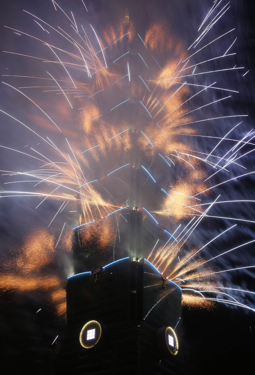 A massive fireworks display launches from the Taipei101 skyscraper during the New Year's Eve celebrations in Taipei, Taiwan, Tuesday, Dec. 31, 2013. (AP Photo/Wally Santana)
