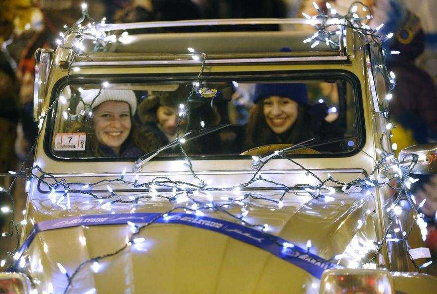 Participants waiting for the start of a parade sit in a Citroen 2CV adorned with lights during New Year's Eve celebrations in Boston, Tuesday, Dec. 31, 2013. (AP Photo/Michael Dwyer)
