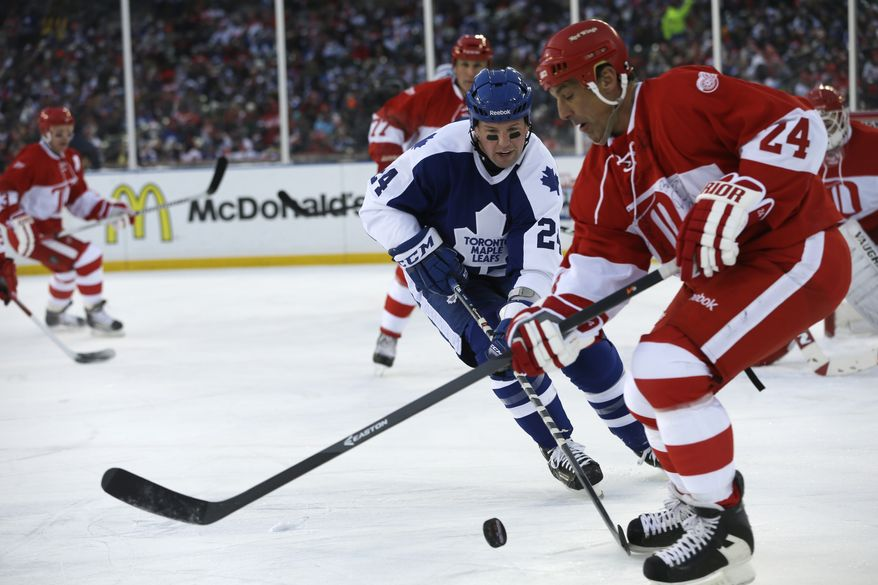 Toronto Maple Leafs defenseman Bryan McCabe closes in on Detroit Red Wings defenseman Chris Chelios during the first period of the Winter Classic Alumni outdoor NHL hockey game at Comerica Park in Detroit, Tuesday, Dec. 31, 2013. (AP Photo/Carlos Osorio)
