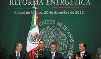 Mexico's President Enrique Pena Nieto greets attendees at the signing ceremony for the approved energy reforms at the National Palace in Mexico City, Friday, Dec. 20, 2013. The sweeping reforms approved by state legislators allow private companies to explore for and produce oil and gas, capping a remarkable series of legislative victories by the Mexican leader. (AP Photo/Eduardo Verdugo)