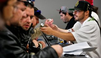 GREEN WEDNESDAY: David Marlow, an employee at the Medicine Man store in Denver, gives a customer at the crowded counter a whiff of a strain of marijuana Wednesday as Colorado began legal retail sales of pot for recreational use. (Associated Press)
