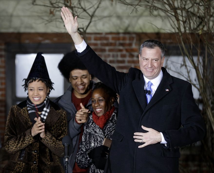 Bill de Blasio, right, waves while standing with his wife Chirlane McCray, second from right, and children Dante and Chiara, after being sworn in as the mayor of New York City at the start of the new year, Wednesday, Jan. 1, 2014, in New York. (AP Photo/Seth Wenig, Pool)