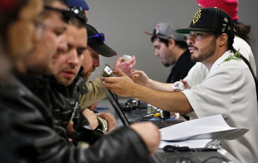 """** FILE ** Employee David Marlow, right, helps a customer, who smells a strain of marijuana before buying it, at the crowded sales counter inside Medicine Man marijuana retail store, which opened as a legal recreational retail outlet in Denver on Wednesday, Jan. 1, 2014. Colorado began retail marijuana sales on Jan. 1, a day some are calling """"Green Wednesday."""" (AP Photo/Brennan Linsley)"""