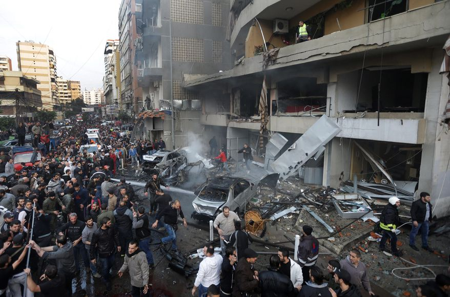 Lebanese gather at the site of a car bomb explosion in a stronghold of the Shiite Hezbollah group at the southern suburb of Beirut Thursday. (Associated Press)