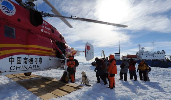 In this file photo provided China's official Xinhnua News Agency, passengers from the trapped Russian vessel MV Akademik Shokalskiy, seen at right, prepare to board the Chinese helicopter Xueying 12 in the Antarctic Thursday, Jan. 2, 2014. (AP Photo/Xinhua, Zhang Jiansong) NO SALES **FILE**