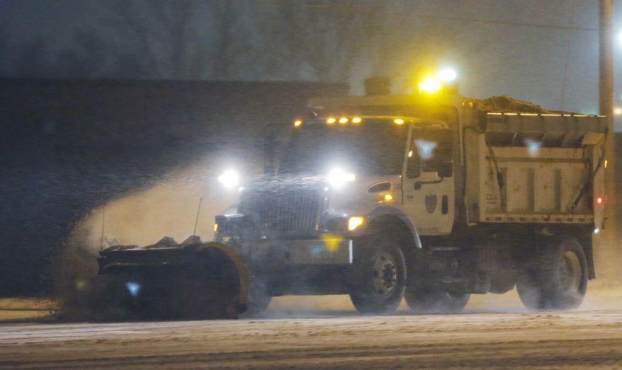A city snow plow clears drifts of snow along U.S. 59 in Lawrence, Kan., Wednesday, Jan. 1, 2014. A winter weather advisory is in effect for the area. (AP Photo/Orlin Wagner)