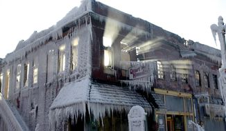 Sunlight streams through the windows of a building which caught on fire in Plattsmouth, Neb., Friday, Jan. 3, 2014, and the water sprayed on it by fire fighters froze. Much of the American northeast and the midwest are suffering from sub-freezing temperatures. (AP Photo/Nati Harnik)