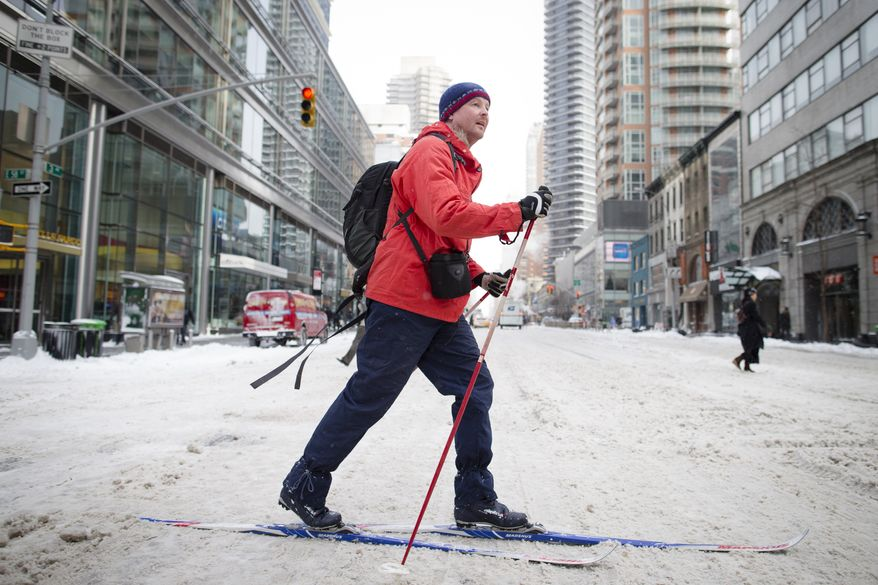 A pedestrian uses his cross-country skies on 58th Street during his morning commute, Friday, Jan. 3, 2014, in New York. New York City public schools were closed Friday after up to 7 inches of snow fell by morning in the first snowstorm of the winter. (AP Photo/John Minchillo)