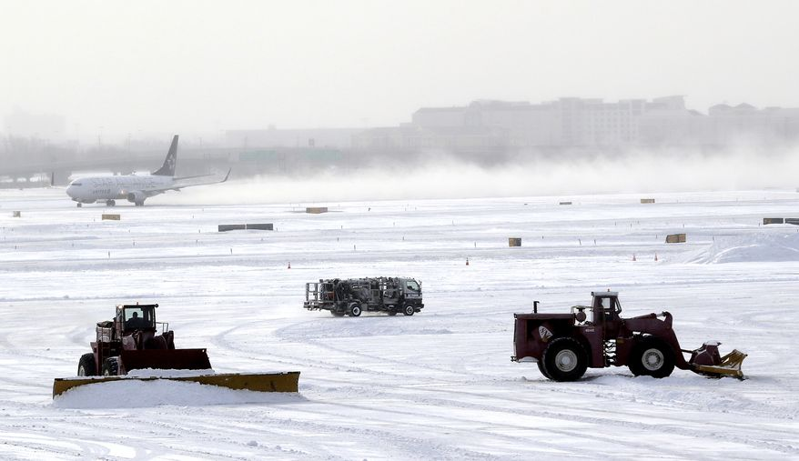 A plane takes off from Newark Liberty International Airport as workers plow the tarmac, Friday, Jan. 3, 2014, in Newark, N.J. New Jersey Gov. Chris Christie declared state of emergency Thursday, urging residents to stay home. Schools were closed as temperatures reached below 20 degrees with wind-chills below zero in some places. (AP Photo/Julio Cortez)