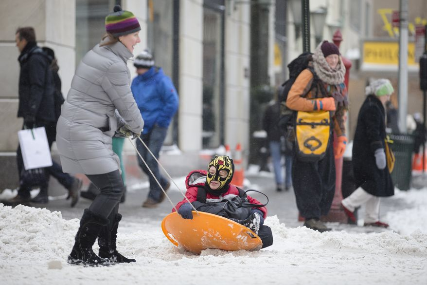Liam Necina is pulled along in a snow sled on 58th Street by his mother Noreen, Friday, Jan. 3, 2014, in New York. New York City public schools were closed Friday after up to 7 inches of snow fell by morning in the first snowstorm of the winter. (AP Photo/John Minchillo)