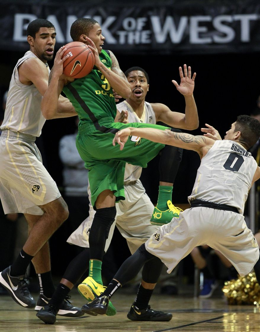 Oregon guard Joseph Young, front center, is surrounded as he drives the lane for a shot by, from back left, Colorado center Josh Scott, and guards Spencer Dinwiddie and Askia Booker in the first half of an NCAA college basketball game, Sunday, Jan. 5, 2014, in Boulder, Colo. (AP Photo/David Zalubowski)