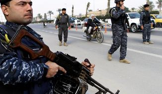 Old Ways: Iraqis have posted checkpoints along roads rather than adopting counterinsurgency practices as taught by U.S. forces, says an architect of the U.S. troop surge that reduced violence in Iraq by 90 percent and led to the military exodus ordered by President Obama in 2011. Trained Iraqi defense forces have since been unable to contain al Qaeda. (Associated Press photographs)
