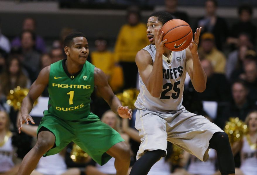Colorado guard Spencer Dinwiddie, right, pulls in the loose ball as Oregon guard Dominic Artis defends in the second half of Colorado's 100-91 victory of an NCAA college basketball game, Sunday, Jan. 5, 2014, in Boulder, Colo. (AP Photo/David Zalubowski)