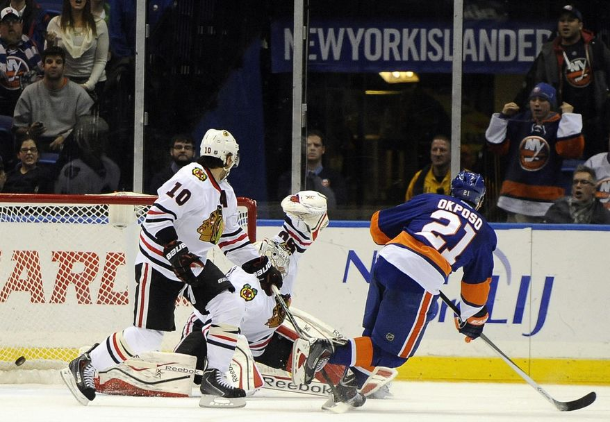 New York Islanders' Kyle Okposo (21) shoots the puck past Chicago Blackhawks goalie Corey Crawford (50) as Blackhawks' Patrick Sharp (10) watches in overtime of an NHL hockey game on Thursday, Jan. 2, 2014, in Uniondale, N.Y. The Islanders won 3-2. (AP Photo/Kathy Kmonicek)
