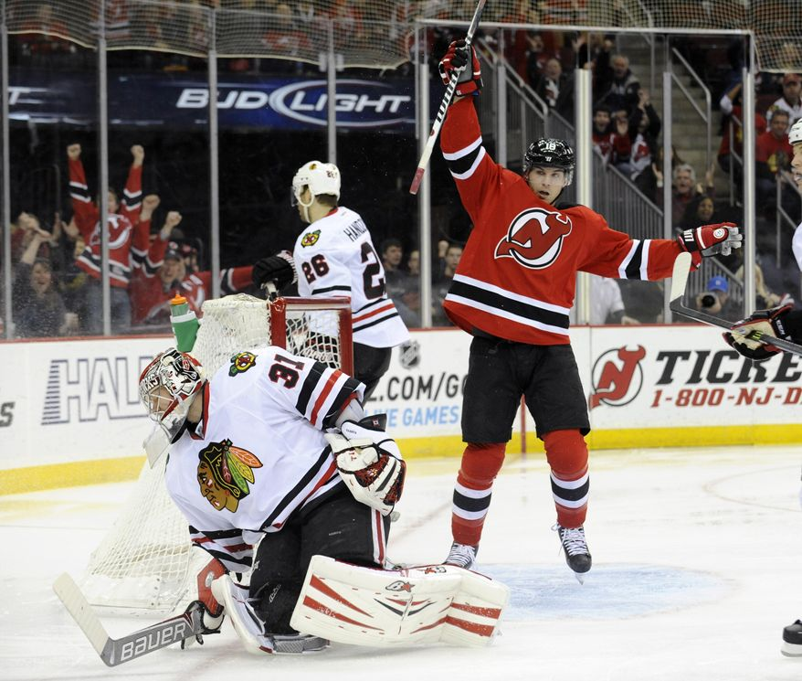 New Jersey Devils' Steve Bernier, right, celebrates a goal by Andy Greene (not shown) as Chicago Blackhawks goaltender Antti Raanta reacts during the second period of an NHL hockey game, Friday, Jan. 3, 2014, in Newark, N.J.  (AP Photo/Bill Kostroun)