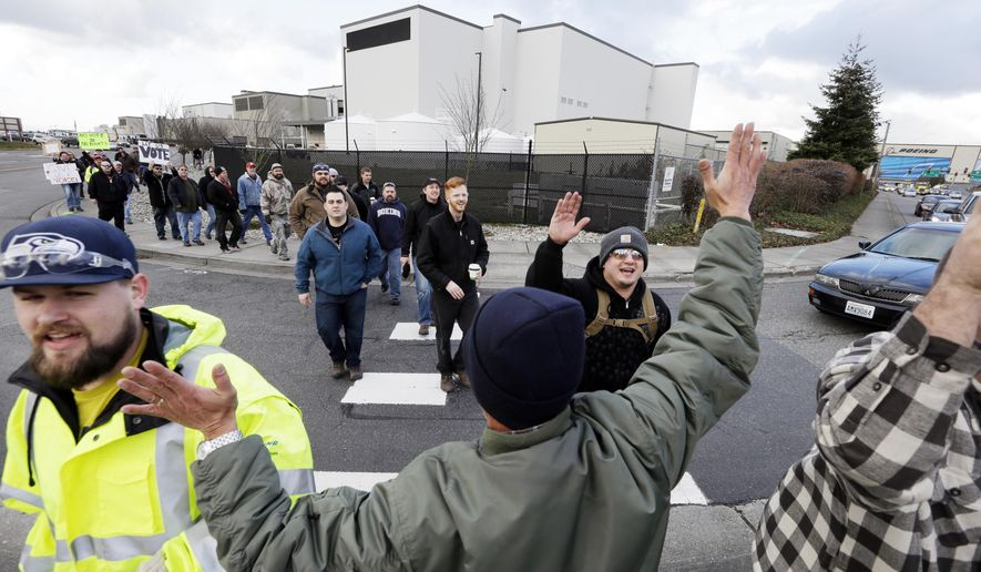 In this Dec. 18, 2013, file photo shows a small group of machinists union members are greeted by a supporter as they march away from a Boeing factory building toward the machinists' union hall in Everett, Wash. (AP Photo/Elaine Thompson, File)