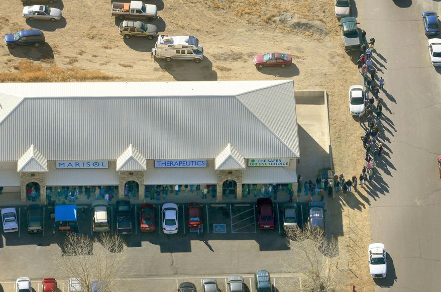 A long line of buyers trails from a store selling marijuana in Pueblo West, Colo, Wednesday, Jan. 1, 2014. The nation's first recreational pot industry opened in Colorado on Wednesday, kicking off a marijuana experiment that will be watched closely around the world. (AP Photo/John Wark)