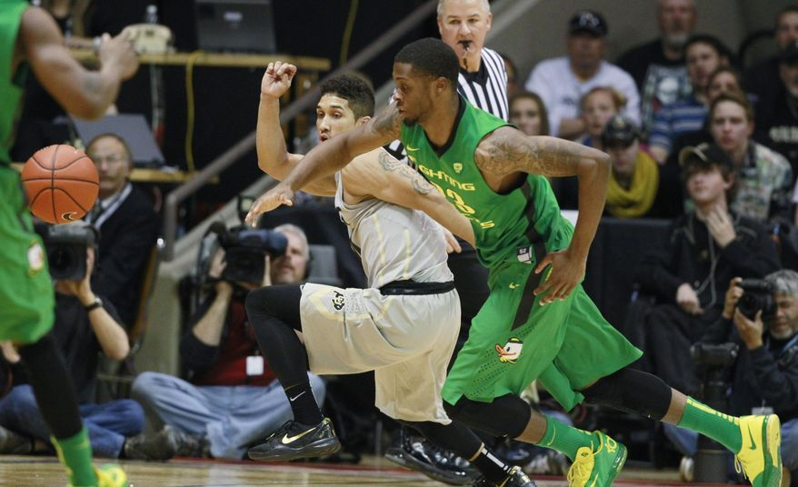 Oregon forward Elgin Cook, front, pursues the loose ball with Colorado guard Askia Booker in the first half of an NCAA college basketball game, Sunday, Jan. 5, 2014, in Boulder, Colo. (AP Photo/David Zalubowski)