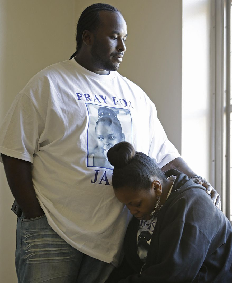 Martin Winkfield places his arm around his wife Nailah Winkfield, mother of 13-year-old Jahi McMath, as they wait outside a courtroom Friday, Jan. 3, 2014, in Oakland, Calif. A federal magistrate was expected to meet Friday with lawyers to try to resolve a dispute over the care ofJahi McMath, who was declared brain dead after tonsil surgery. (AP Photo/Ben Margot)