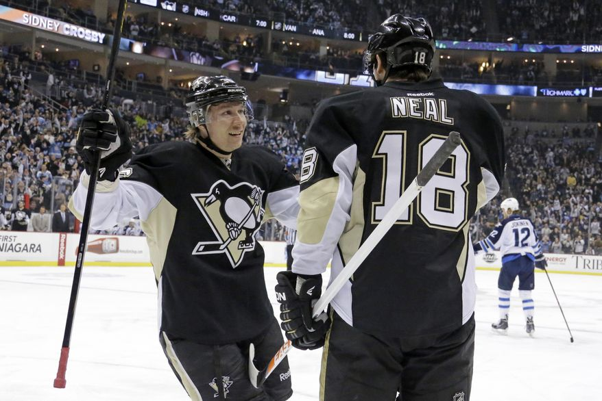 Pittsburgh Penguins' James Neal (18) celebrates with Jussi Jokinen (36) after getting his second goal in second period of an NHL hockey game against the Winnipeg Jets in Pittsburgh, Sunday, Jan. 5, 2014. (AP Photo/Gene J. Puskar)