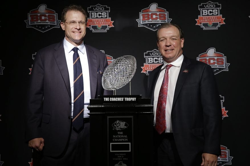 Auburn head coach Gus Malzahn, left, and Florida State head coach Jimbo Fisher pose with The Coaches' Trophy during a news conference for the NCAA BCS National Championship college football game Sunday, Jan. 5, 2014, in Newport Beach, Calif. Florida State plays Auburn on Monday, Jan. 6, 2014. (AP Photo/David J. Phillip)