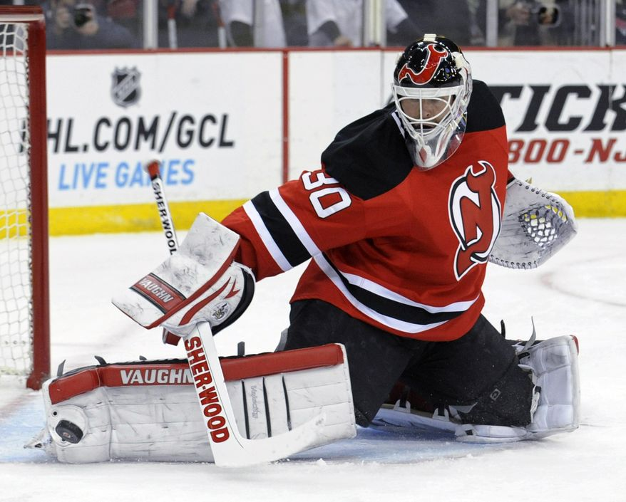 New Jersey Devils goaltender Martin Brodeur deflects the puck during the first period of an NHL hockey game against the Chicago Blackhawks on Friday, Jan. 3, 2014, in Newark, N.J. (AP Photo/Bill Kostroun)