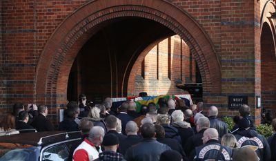 """Mourners carry the coffin of great train robber Ronnie Biggs into the chapel at Golders Green Crematorium in London, Friday Jan. 3, 2014. Biggs was a member of a gang that stole 2.6 million pounds from a Glasgow-to-London mail train in August 1963, in what was called the """"heist of the century."""" He spent decades in exile in Brazil before agreeing to return to Britain, and prison, in 2001. (AP Photo/Sang Tan)"""