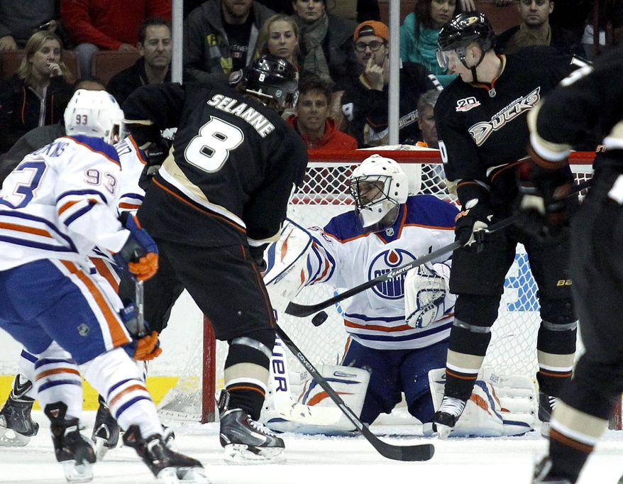 Edmonton Oilers goalie Ilya Bryzgalov, center, of Russia, stops a defection by Anaheim Ducks right wing Corey Perry, right, with right wing Teemu Selanne (8), of Finland, looking for the rebound during the first period of an NHL hockey game, Friday, Jan. 3, 2014, in Los Angeles.  (AP Photo/Alex Gallardo)