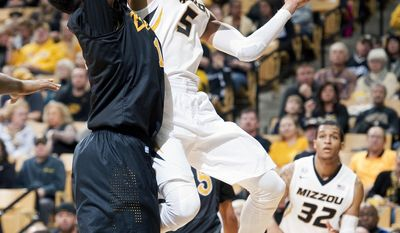 Missouri's Jordan Clarkson, center, passes the ball around Long Beach State's David Samuels, left, as Jabari Brown, right, stands near during the first half of an NCAA college basketball game Saturday, Jan. 4, 2014, in Columbia, Mo. (AP Photo/L.G. Patterson)