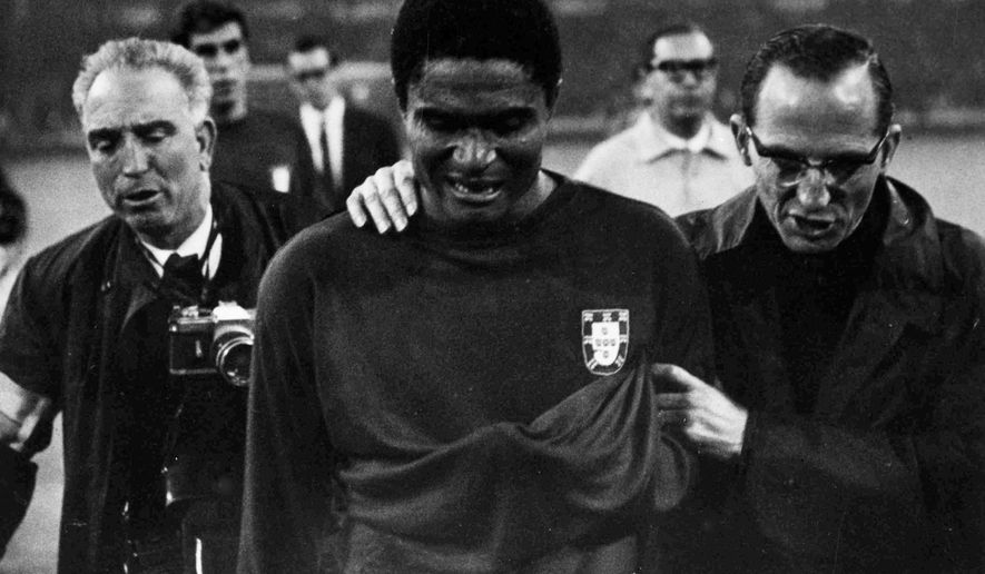 FILE - In this July 26, 1966 file photo, Portugal's star player Eusebio is led from the pitch in tears after England defeated Portugal 2-1 in the semifinal of the World Cup at Wembley, London. Eusebio, the Portuguese football star who was born into poverty in Africa but became an international sporting icon and was voted one of the 10 best players of all time, has died of heart failure aged 71, Sunday, Jan. 5, 2014. (AP Photo/Bippa, File)