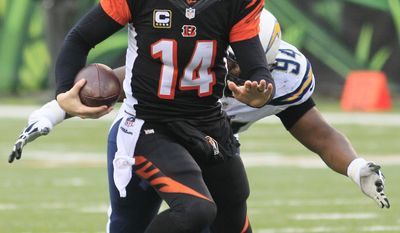 Cincinnati Bengals quarterback Andy Dalton (14) is chased by San Diego Chargers defensive end Corey Liuget in the second half of an NFL wild-card playoff football game on Sunday, Jan. 5, 2014, in Cincinnati. (AP Photo/Tom Uhlman)