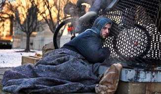 Nicholas Simmons, 20, of Greece, N.Y., warms himself on a steam grate with three homeless men by the Federal Trade Commission, just blocks from the Capitol, during frigid temperatures in Washington, Saturday, Jan. 4, 2014. (AP Photo/Jacquelyn Martin) ** FILE **