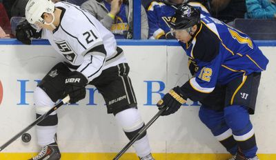 St. Louis Blues' Derek Roy (12) and Los Angeles Kings' Matt Frattin (21) reach for a loose puck during the first period of an NHL hockey game on Thursday, Jan. 2, 2014, in St. Louis. (AP Photo/Bill Boyce)