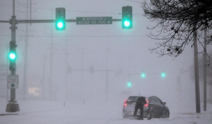 """A Crestwood motorist tries to get his car moving along Watson Road in St. Louis as heavy snow falls on Sunday, Jan. 5, 2014. Snow-covered roads, high winds and ice were creating dangerous driving conditions from Missouri to Delaware on Sunday ahead of a """"polar vortex"""" that'll bring below-zero temperatures not seen in years to much of the nation in the coming days, likely setting records. (AP Photo/St. Louis Post-Dispatch, Robert Cohen)  EDWARDSVILLE INTELLIGENCER OUT; THE ALTON TELEGRAPH OUT"""