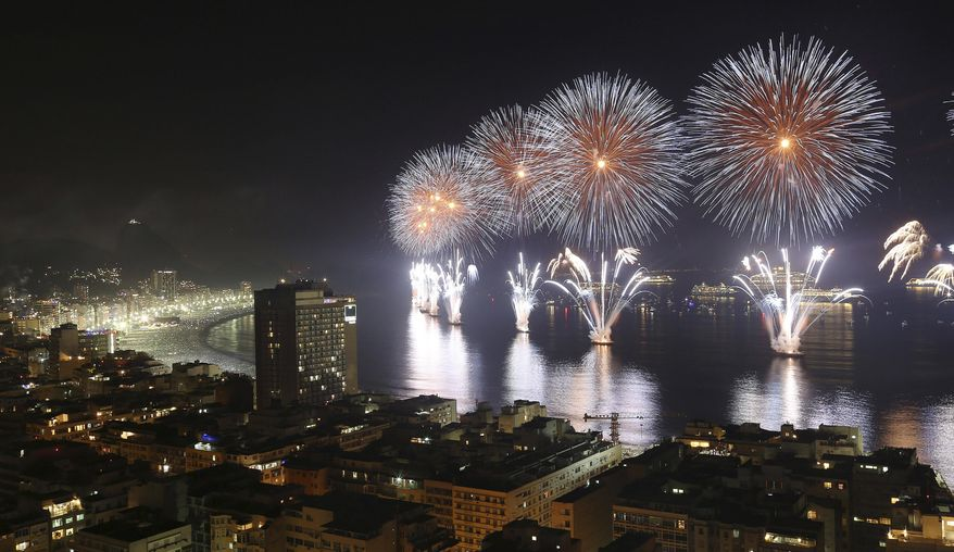 In this Wednesday, Jan. 1, 2014 photo, fireworks light the sky over Copacabana beach during New Year's Eve celebrations in Rio de Janeiro, Brazil. (AP Photo/Leo Correa)