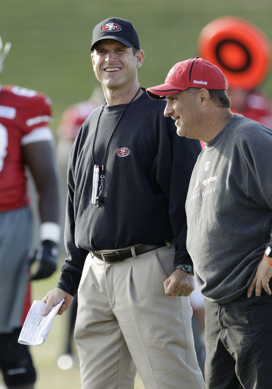 San Francisco 49ers coach Jim Harbaugh, left, and defensive coordinator Vic Fangio, right, smile during the NFL football team's training camp in Santa Clara, Calif., Thursday, Aug. 4, 2011. (AP Photo/Paul Sakuma)