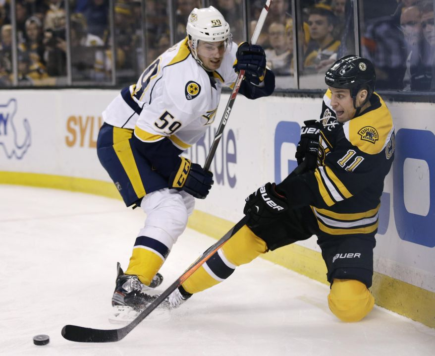 Boston Bruins center Gregory Campbell (11) centers the puck from behind the goal as he is pressured by Nashville Predators defenseman Roman Josi (59) during the second period of an NHL hockey game, Thursday, Jan. 2, 2014, in Boston. (AP Photo/Charles Krupa)
