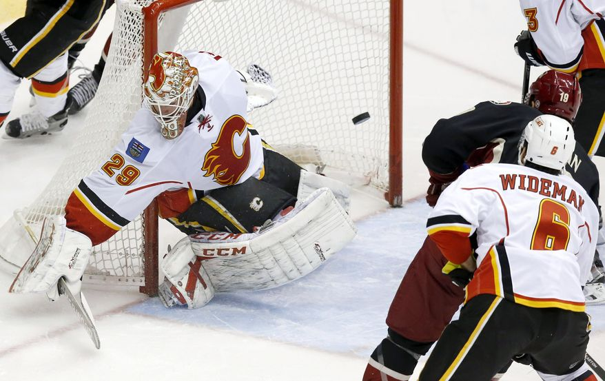Calgary Flames' Reto Berra (29), of Switzerland, gives up a goal to Phoenix Coyotes' Shane Doan (19) as Flames' Dennis Wideman (6) defends during the second period of an NHL hockey game, Tuesday, Jan. 7, 2014, in Glendale, Ariz. (AP Photo/Ross D. Franklin)