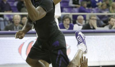 Kansas State guard Omari Lawrence (12) keeps control of the ball after knocking over TCU guard Charles Hill during the first half of an NCAA basketball game in Fort Worth, Texas, Tuesday, Jan. 7, 2014.  (AP Photo/LM Otero)