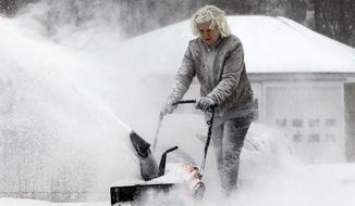 Lynette Johnson snow blows her Springville,NY,driveway in the bitter wind and cold on,Monday, Jan. 6, 2014.(AP Photo/The Buffalo News, Harry Scull Jr.)